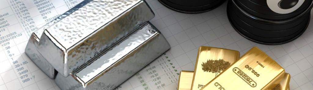 3 Goldbarren und 3 Silberbarren auf einem Schreibtisch gestapelt.