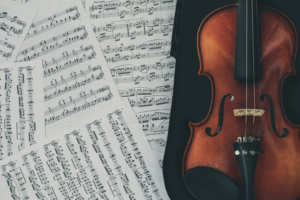 Eine hochwertige Violine liegt im Koffer daneben einige Notenblätter.