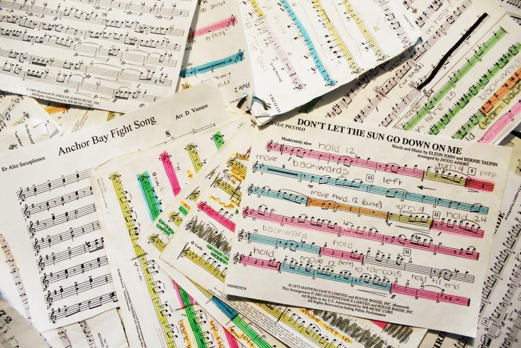 Viele Notenblätter mit farblichen Markierungen und Randkritzeleien liegen kreuz und quer übereinander.