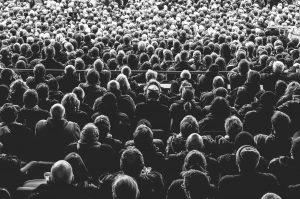Menschenmenge sitzend in eine Richtung schauend