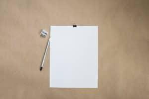 Weisses Blatt Papier auf Schreibtisch daneben ein Bleistift